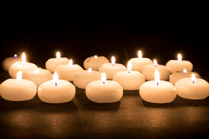 Several white candles at a black background